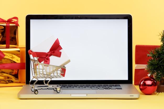 Concepto de compras navideñas en línea en la pantalla del portátil. pantalla blanca en la computadora y regalos con bolsas de papel cerca.