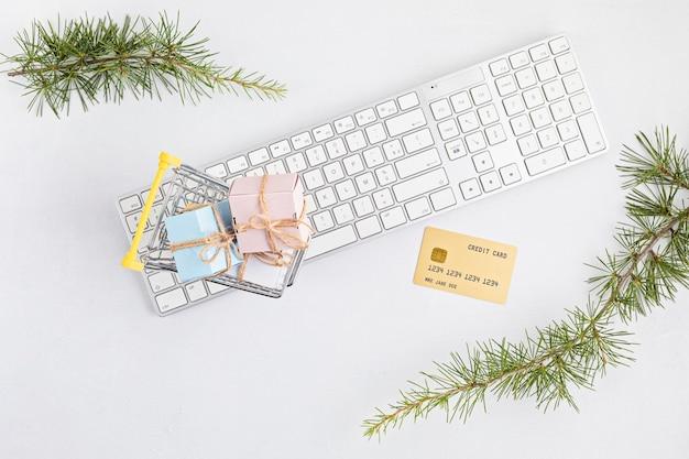 Concepto de compras navideñas online con cajas de regalo, teclado y tarjeta de crédito dorada. vista superior, endecha plana