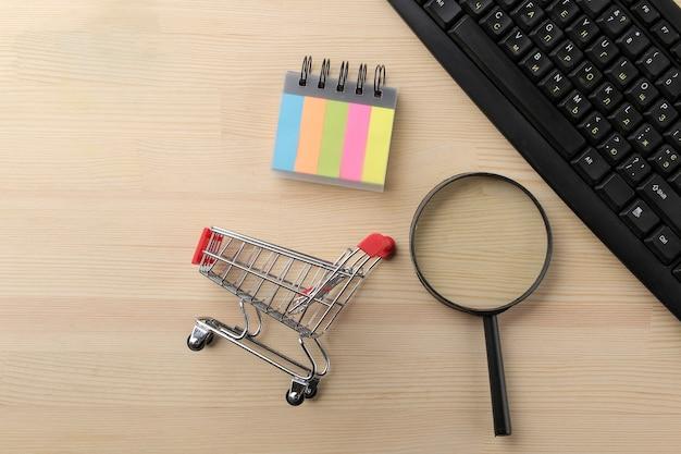 El concepto de compras online. composición con una lupa y un carrito de la compra en el fondo de la mesa