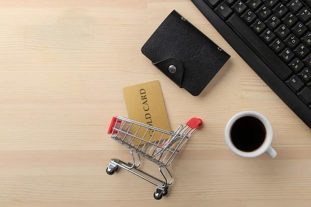 El concepto de compras online. composición con una tarjeta de descuento y un carrito de la compra en el fondo de la mesa.