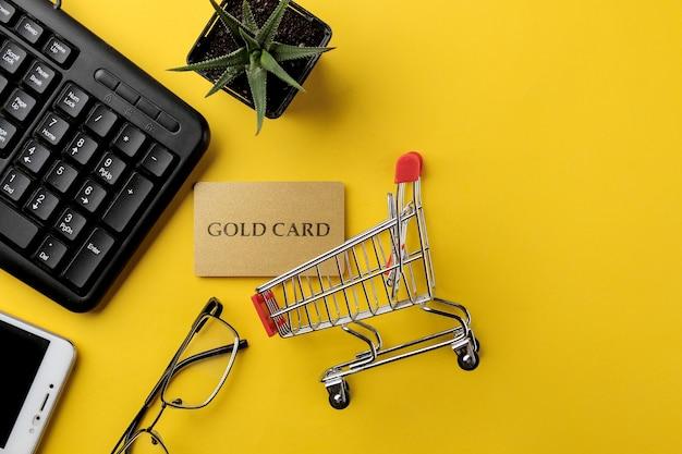 El concepto de compras online. composición con una tarjeta de descuento y un carrito de la compra y un teléfono sobre un fondo amarillo