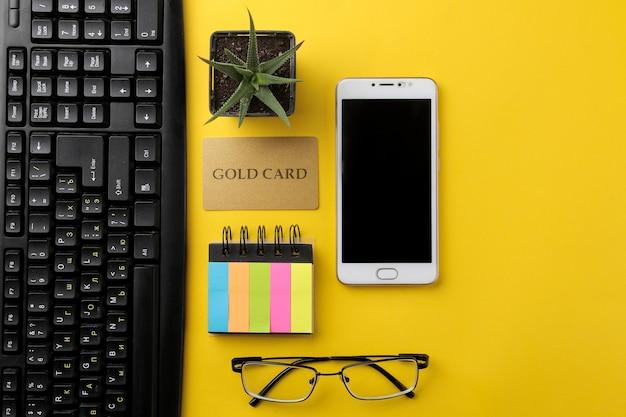 El concepto de compras online. composición con una tarjeta de descuento y un teléfono sobre un fondo amarillo