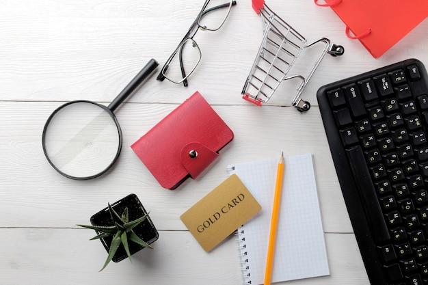 El concepto de compras online. composición con tarjetas de descuento y carrito de la compra sobre un fondo claro.