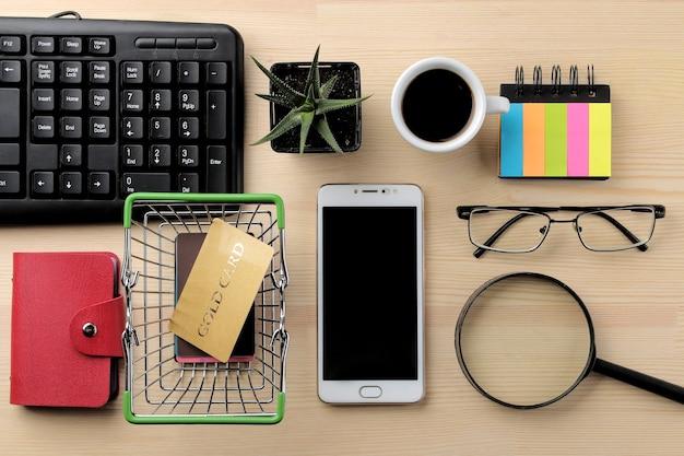 El concepto de compras online. composición con tarjetas de descuento y un carrito de la compra y un teléfono en el fondo de la mesa