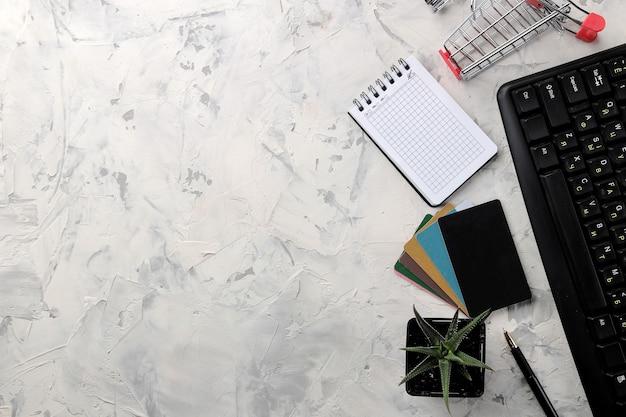 El concepto de compras online. composición con tarjetas de descuento y carrito de la compra y teléfono sobre un fondo claro.