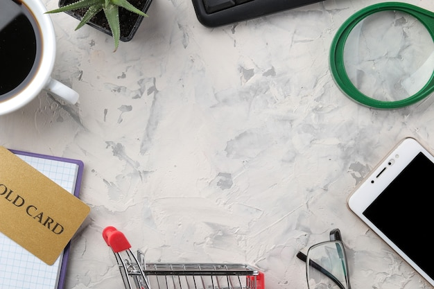 El concepto de compras online. composición con tarjetas de descuento y teléfono sobre un fondo claro. vista desde arriba