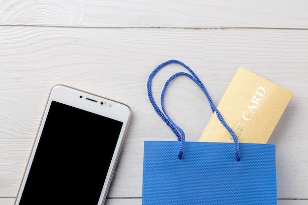El concepto de compras online. composición con tarjetas de descuento y teléfono sobre un fondo claro.