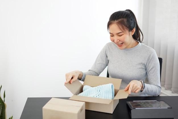 Concepto de compras online una mujer sonriente desembalaje de un paquete que llega para comprobar los productos que compró después de esperar con un esfuerzo.