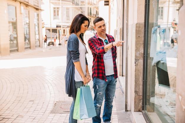 Concepto de compras con pareja mirando tiendo de moda