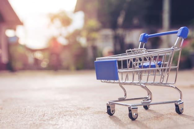 Concepto de las compras: pequeño juguete vacío azul del carro de la compra en piso concreto. mercado de compras