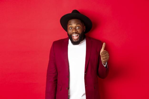 Concepto de compras y personas de navidad. guapo hombre negro barbudo en chaqueta de fiesta mostrando el pulgar hacia arriba, mirando sorprendido y satisfecho, fondo rojo.