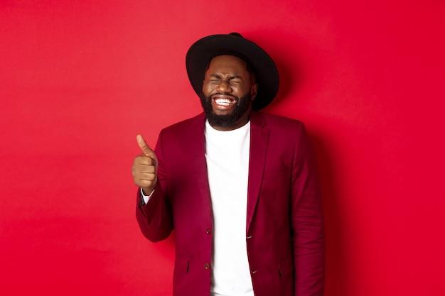 Concepto de compras y personas de navidad. guapo hombre negro barbudo en chaqueta de fiesta mostrando el pulgar hacia arriba, riendo y divirtiéndose, de pie sobre fondo rojo.