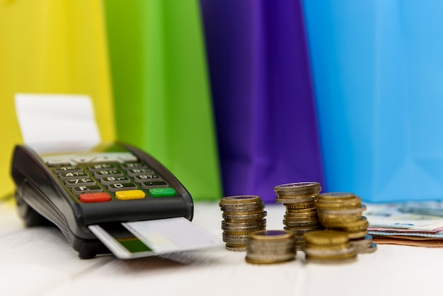Concepto de compras con terminal, tarjeta y monedas de euro