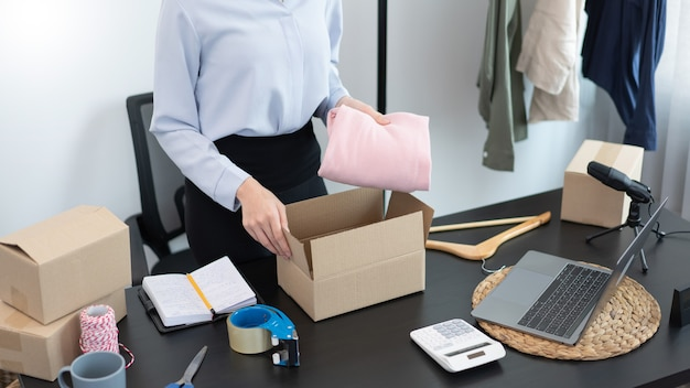 Concepto de compras en vivo una mujer comerciante que empaca productos en cajas después de recibir pedidos de los clientes.