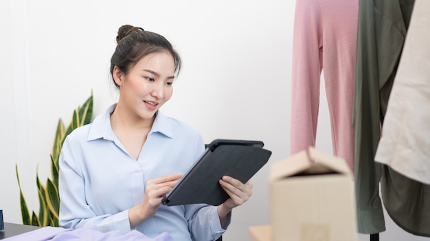 Concepto de compras en vivo una mujer comerciante que usa un lápiz de tableta deslizando la tableta para verificar los pedidos del día.