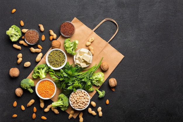 Concepto: compre alimentos saludables y limpios. fuente de proteínas para vegetarianos: verduras, frutos secos, semillas y legumbres vista superior sobre un fondo negro con una bolsa de papel.