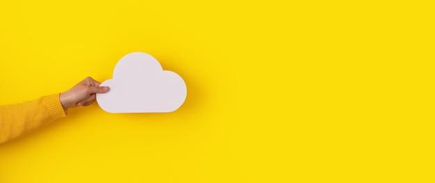 Concepto de computación en la nube, mano sujetando la nube sobre fondo amarillo, almacenamiento en la nube, imagen panorámica