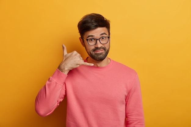 Concepto de comunicación móvil. hombre sin afeitar hace un gesto de llamarme, habla por celular imaginario, tiene una expresión positiva amistosa, usa lentes transparentes y un jersey rosa, aislado en una pared amarilla