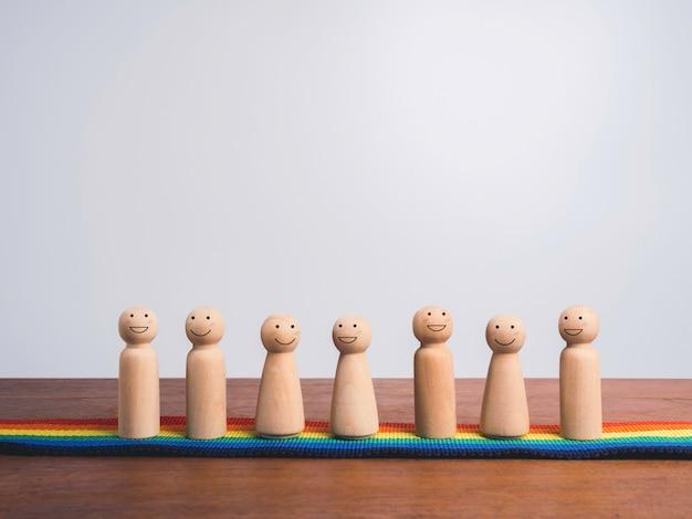 Concepto de comunidad lgbt. grupo de figuras de madera con caras sonrientes felices parados juntos en la bandera del arco iris, desfile del orgullo en la mesa de madera y fondo blanco con espacio de copia.