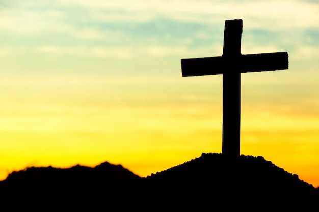 Concepto conceptual cruz religión símbolo silueta en la naturaleza sobre la puesta del sol o el amanecer del cielo