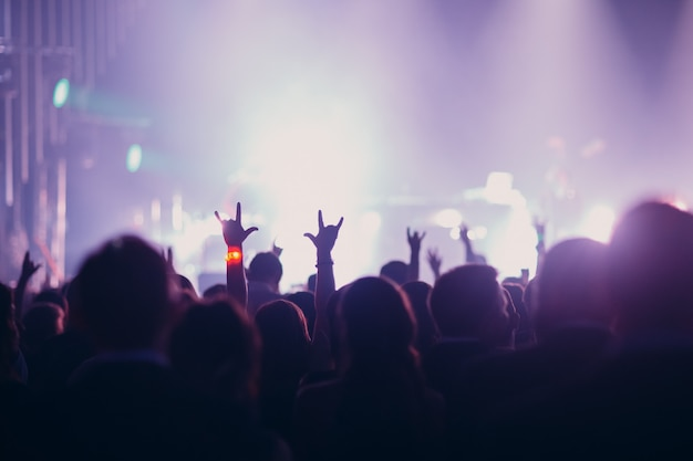 Concepto de concierto, evento o fiesta. personas con las manos en alto en la escena, reflector, luz de color lila.