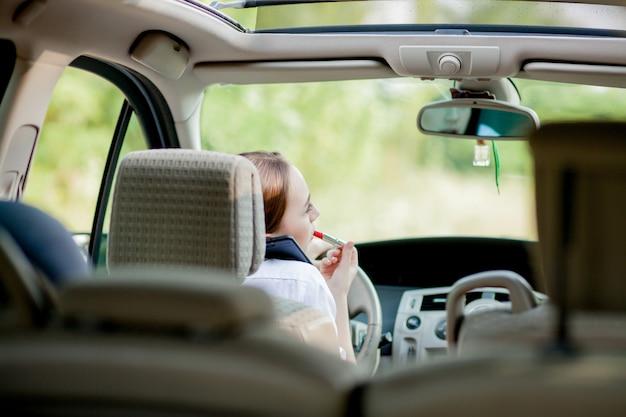 Concepto de conducción peligrosa. conductor joven pelirroja adolescente pintando sus labios haciendo aplicar maquillaje mientras conduce el auto