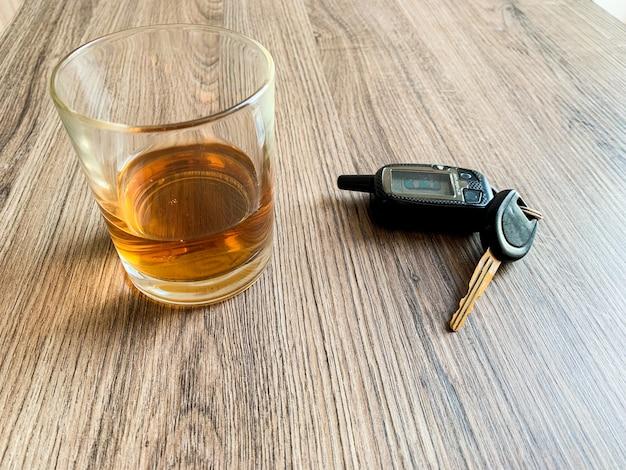 Concepto de conducir ebrio. vaso con whisky y la llave del coche sobre la mesa.