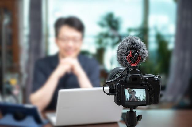 Concepto de conferencia en línea. hombre asiático de mediana edad dando conferencias en línea en casa.