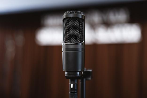 Concepto de conferencia, un pequeño micrófono negro en el escenario