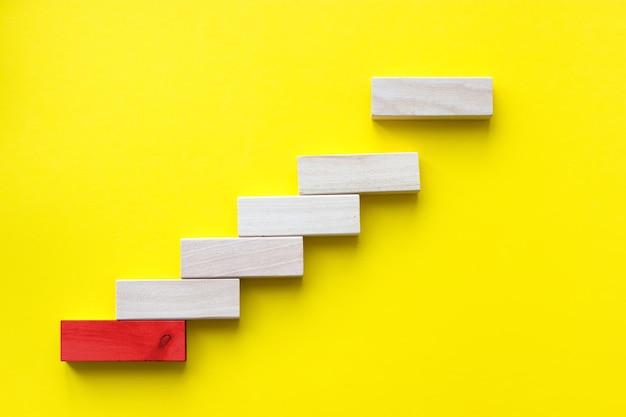 Concepto de construcción de la base del éxito. apilamiento de bloques de madera roja como escalera, éxito en los negocios