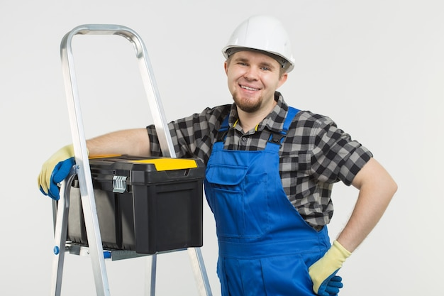 Concepto de construcción, construcción y trabajadores - constructor masculino caucásico con casco blanco.