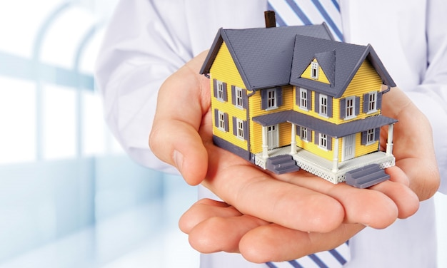 Concepto de construcción, hipoteca, bienes raíces y propiedad - cierre de mano sosteniendo el modelo de la casa