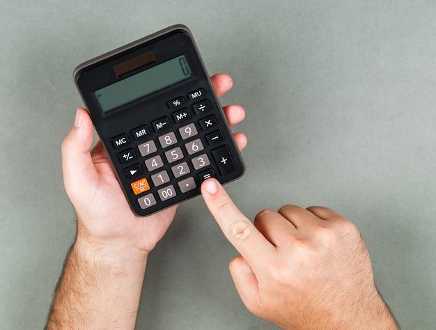 Concepto de contabilidad y cálculo en la vista superior de la superficie gris. alguien calculando algo. imagen horizontal