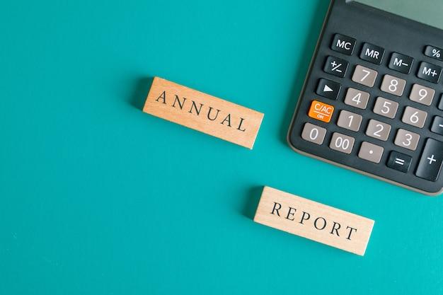 Concepto de contabilidad financiera con bloques de madera, calculadora en mesa turquesa endecha plana.