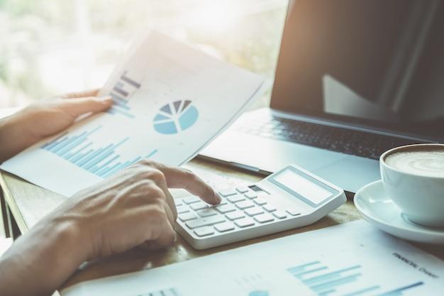 Concepto de contable el contador está presionando la calculadora para calcular la precisión del presupuesto de inversión con el uso de computadora portátil y datos de documentos para el análisis.