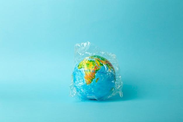 Concepto de contaminación de bolsas de plástico. globo terráqueo en una bolsa de plástico sobre un fondo coloreado. plásticos y contaminación por desechos océanos, naturaleza