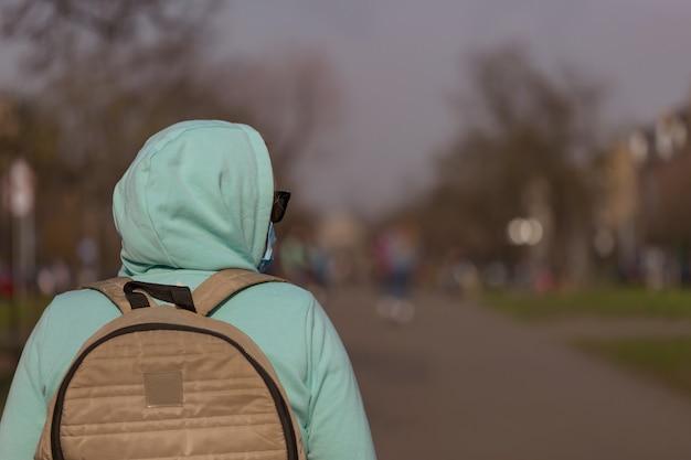 Concepto de coronavirus chica con máscara protectora contra enfermedades y guantes protectores está en la calle