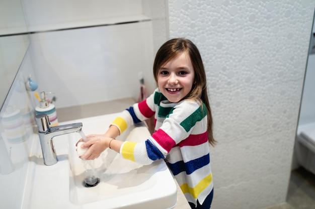 Concepto de coronavirus covid-19. chica lavándose las manos en el baño con jabón antibacteriano.
