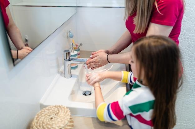 Concepto de coronavirus covid-19. madre e hija se lavan las manos en el baño con jabón antibacteriano.