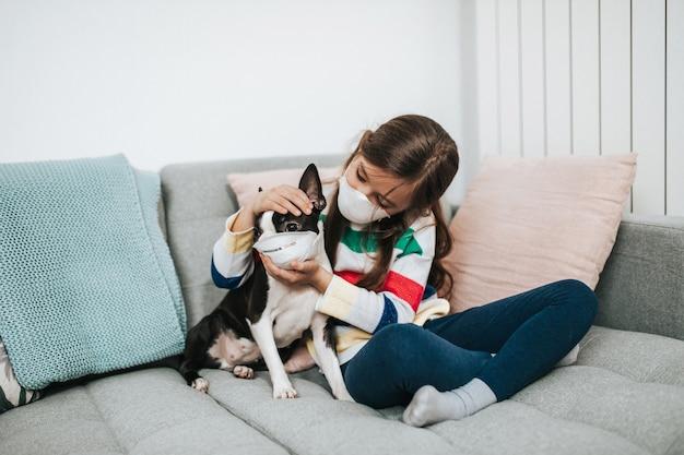 Concepto de coronavirus covid-19. niña y su perro con máscaras protectoras en la cara juegan a vivir mientras están en cuarentena.