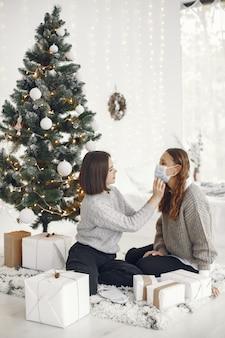 Concepto de coronavirus y navidad. la mujer ayuda a su amiga con una máscara.