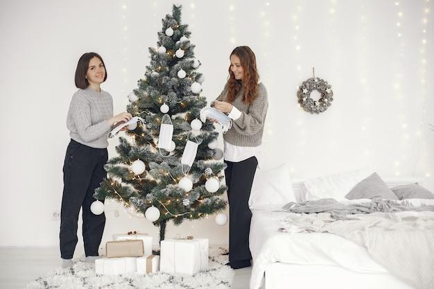 Concepto de coronavirus y navidad. mujeres en casa. dama con un suéter gris.