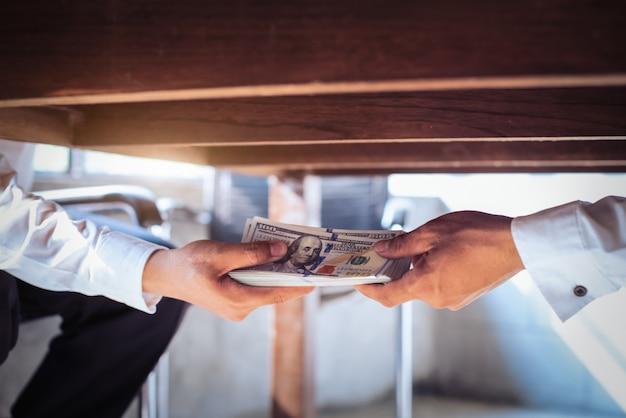 Concepto de corrupción, hombre de negocios que toma soborno del hombre debajo de la mesa