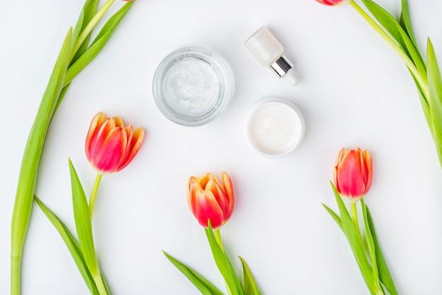 Concepto de cosmética casera orgánica natural. productos para el cuidado de la piel, remedios y belleza: envases con crema y suero entre flores de tulipán rojo primaveral sobre superficie blanca. lay flat, copia espacio para texto