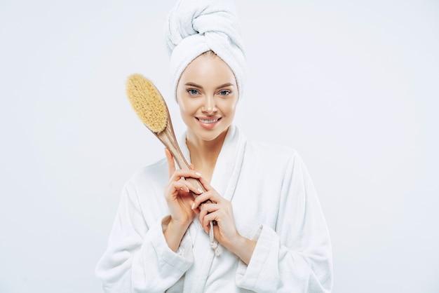 Concepto de cosmetología, peeling, spa y aseo. mujer europea joven complacida con piel sana, sonrisa suave, sostiene un cepillo de masaje para el cuerpo y los pies, se preocupa por sí misma, vestida con una bata de baño