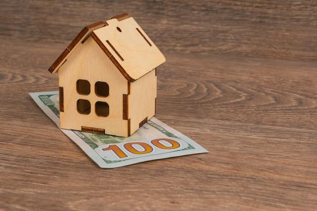 Concepto de costos de servicios públicos caros con modelo de casa de madera y billetes de 100 dólares