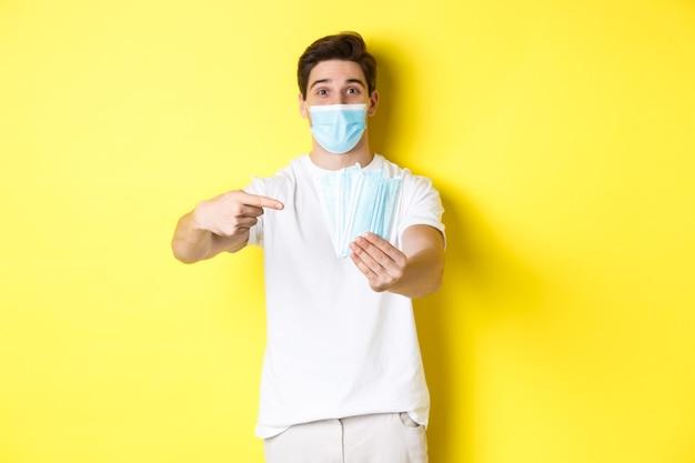 Concepto de covid-19, cuarentena y medidas preventivas. hombre caucásico joven que da máscaras médicas para usted, de pie contra el fondo amarillo.