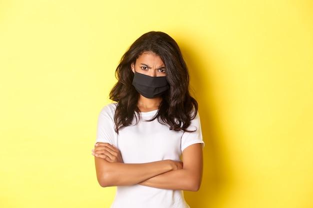 Concepto de covid-19, distanciamiento social y estilo de vida. chica afroamericana enojada y ofendida, con mascarilla, estar enojada con alguien, cruzar los brazos en el pecho y fruncir el ceño, fondo amarillo