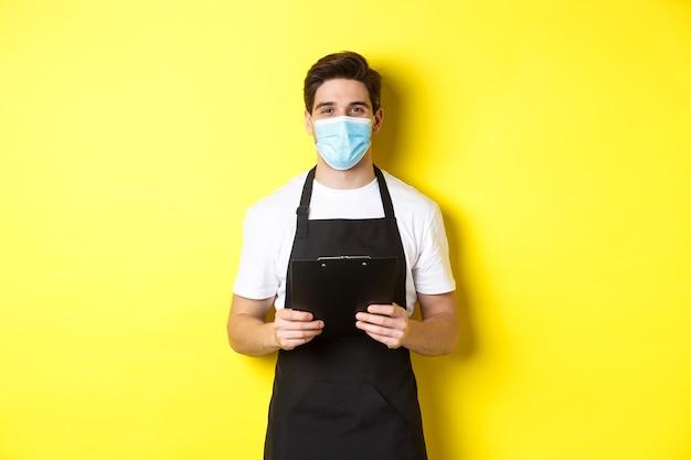 Concepto de covid-19, pequeña empresa y cuarentena. vendedor en delantal negro y máscara médica con portapapeles, trabajando en la tienda, de pie sobre fondo amarillo.