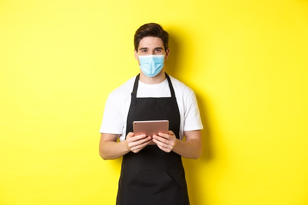 Concepto de covid-19, pequeña empresa y pandemia. camarero en delantal negro y máscara médica tomando orden, sosteniendo tableta digital, de pie sobre fondo amarillo.